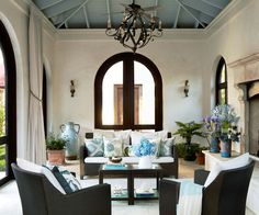 Stone walls and a dramatic pitched ceiling make a wow-worthy statement in this sunporch. The ceiling was painted blue, which draws the eye upward and emphasizes the height of the room. The blue color of the ceiling is repeated and echoed through the various patterned throws on the sofa and chairs.
