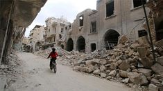 A boy rides his bike alone up the road with tons of rubble.  Photo by: Al Jazeera