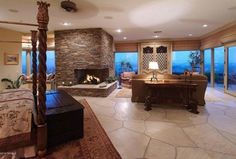 Country Master Bedroom with Console table, French doors, stone fireplace, slate floors, Custom canopy bed, Area rug