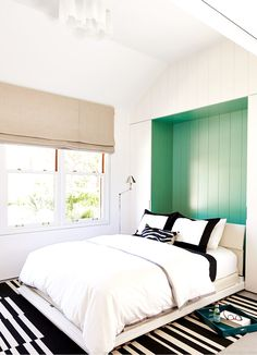 Bedroom with green statement wall and black and white pillows