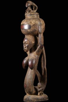 This is a Mami Wata statue from the Baule people of Ivory Coast. Mami aawata or mermaid is a popular goddess in Africa representing the water spirit. This sculpture shows the spirit in one of its popular forms: as a woman-fish hybrid, emerging from the water the waves bearing a basket of wealth.