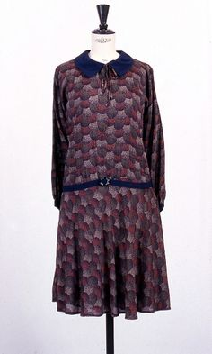 Dress ca 1927 A day dress of printed spun rayon with a pattern of overlapping humps with speckles in red, brown, orange on blue.