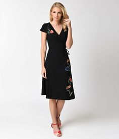 Grace us with florals, gals! The Primrose Dress is a stunning 1950s style wrap dress from Voodoo Vixen crafted in the softest knit fabric blend. An elegant aura, this sultry black piece features a V-neckline with sweet cap sleeves and boasts bright embroi