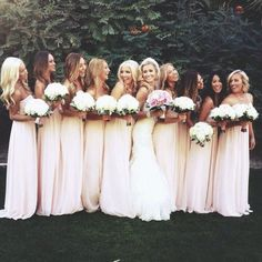 Bride has pink bouquet, bridesmaids have white.