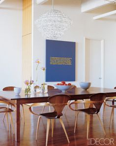 A dining area with retro look - wooden, clean-design table set, crystal chandelier, monochrome large poster art, on white walls/high ceilings