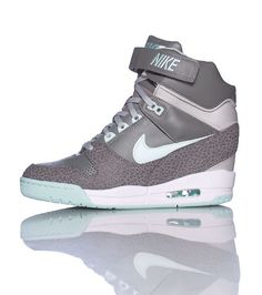 NIKE Women's high top sneaker Lace up closure Lace up closure with velcro strap Textured leather accents on midsole Cushioned sole Green glow accents