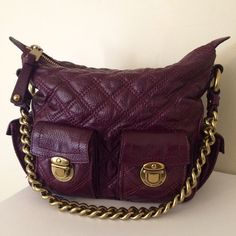 """Marc Jacobs Bordeaux Icy Multipocket APPROXIMATE MEASUREMENTS   9""""W across base, 11""""W across top x 9""""H x 4""""D with a 9"""" strap drop   DETAILS   Brass gold hardware, two front pushlock pockets, one pushlock pocket on either side, top zip closure, red suede lining, one interior zip pocket   CONDITION   The interior lining has a few small spots but is clean. Some scratches/wear on the hardware and small scuffs throughout, mostly on the bottom corners. Icy leather has a slight sheen to it…"""