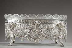 Silver jardiniere composed of a cut-crystal, oval bowl resting in a silver frame. The scalloped edge of the crystal bowl is decorated with radiating and diamond-shaped patterns. The silver frame is...