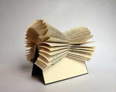 This book sculpture is made of the book: Akte X (The X-Files) A book about the TV-series (in german). Each book is numbered, signed and stamped with my logo on the page with titel. You can still read the book, if you want. Since it is only folded and not glued, you could open the pages, read it, and than refold it. The perfect gift for Bibliophiles. On the bookshelf, Sideboard, coffee table... You can also hang it on the wall. For Book Statements on request: Since I live in Germany,...
