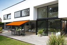 This burnt orange swing arm awning is a wonderful accent to this modern house