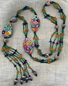 Sautoir necklace with Antique Giant Venetian Millefiori beads, antique forest green Venetian bugle beads, antique jet, faceted onyx rondelle beads, and Baltic amber.
