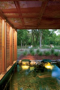 Heavy Metal House  Hufft Projects  Joplin, Missouri  In the backyard, a pond flows from a waterwall. Perforated metal panels clad the facade and fold up to create a brise-soleil on this side of the house.    http://archrecord.construction.com/residential/recordhouses/2012/Heavy-Metal-House.asp