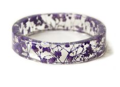 Real tiny Purple Flowers have been handpicked, dried and embedded into resin and shaped into this one of a kind bracelet.