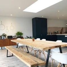 Open plan kitchen dining, navy blue kitchen. Large wooden scaffolding plank table and bench. Mid century sideboard, roof light and eames chairs