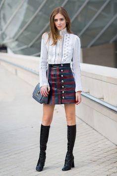 A blogueira Chiara Ferragni em look trendy, com saia listrada de botões e botas over the knee.