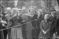 War Fair: Holidays at Home at a fete in Russell Square, London, 1943. A woman plays a shooting game at the fair in Russell Square. She is assisted by a man who explains that she must shoot the corks with which the gun is loaded at cigarettes. Other members of the public look on. Bunting can just be seen in the background. #wartime #WW2 #history