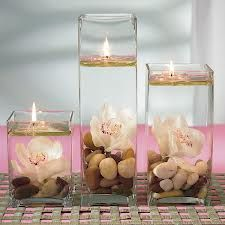 table decorations, love the stones at the bottom with one flower, water abd floating candle...could put in less liquid and use lantern fuel with a glass tube and wick to last for hours and hours