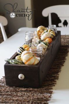 Mix and match different gourds to fill a DIY statement piece for any dining room table. For an extra rustic touch, add mason jars with candles inside of them.  See more at Shanty2Chic.