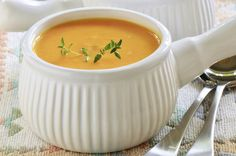 Creamy carrot and sweet potato soup with sprig of thyme in white ribbed soup bowl