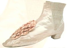 "White silk satin ""congress"" boot with pink satin cockades, American, c. 1865."
