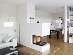Fertighaus am Hang: Helles Wohnzimmer mit dreiseitigem Kamin