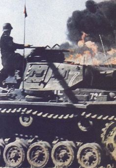 The commander of a Panzer 3 watches as a large explosion and resulting  fire that rages in the background. The standard grey puts this vehicle in the early stages of Germanys attempt conquer European countries.