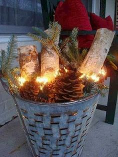 Zinc Basket filled with logs, greens, pinecones and lights.