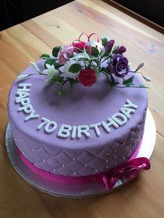 Simple 70th Birthday cake with a few sugar craft flowers.