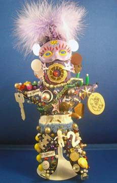 """Lois Simbach - Mardi Gras """"Ju-Ju"""" Queen Be Happy  -  $85 Ju-Ju doll is covered with hand-sewn beads, trinkets, antique and new found objects. (no glue used). This Ju-Ju has an old wooden nickel stamped """"Be Happy"""". Mask is hand-painted porceline. Comes with a doll stand or can be hung on the wall."""