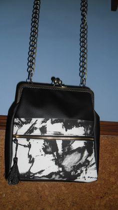 Bolso de skay con boquilla y cadena para colgar.