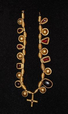 Necklace strung with an alternating sequence of irregular gold and cabochon garnet pendants, gold 'bullae' and biconical gold wire spacer beads. Early Anglo-Saxon 7thC.