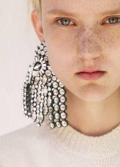Bold earrings and slick back hair.