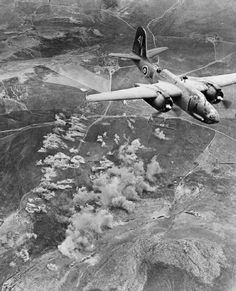 Douglas A-20C, 42-33229 'A', flys over the target area as bombs explode on enemy armoured units on the slopes of Djebel Bou Kournine, Tunisia, during a raid by 30 Bostons of No. 326 Wing RAF against 10th Panzer Division units which were holding up the advance of the 6th Armoured Division to Tunis. 1942