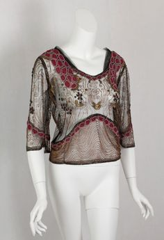 Beaded net overblouse,  made from black net, the top is embellished with bead work and bronzed metallic embroidery, worn over one of the slender gowns that became fashionable just before WWI, c.1912.