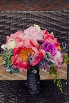 Colorful bouquet designed with coral and watermelon peonies, peach and magenta garden roses and orchids.