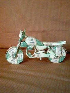 A motor bike very cutely designed and folded with Indian currencies.   A wonderful hand work neatly arranged with all the required parts.  The