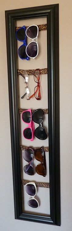 Eyewear in a Picture Frame using ribbon or material scraps across to hang your sunglasses on.