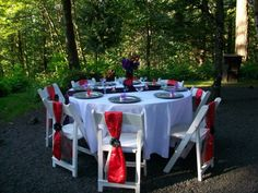 White polyester tablecloth with a eggplant overlay on it, with red and white sashes on the chair's