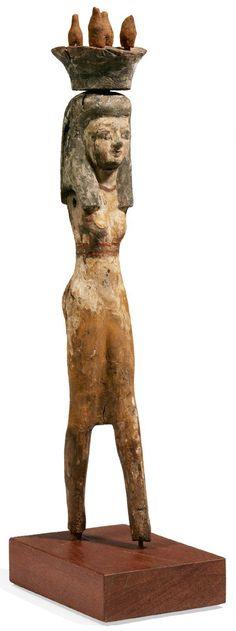 PORTEUSE D'OFFRANDES. Statuette représentant une femme debout, dans l'attitude de la marche apparente, vêtue d'une robe moulante à bretelles. Elle est coiffée de la perruque tripartite surmontée d'une corbeille contenant quatre jarres. Bois stuqué polychrome. Égypte, Moyen Empire.