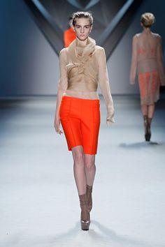 Nude organza multi-layer flange harness over nude silk chiffon long sleeve top with tangerine melton bermuda short.