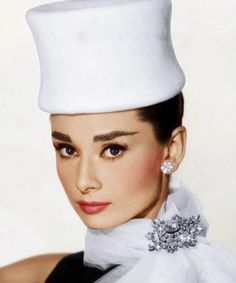 """The actress Audrey Hepburn photographed by Bud Fraker at the Paramount Studios for the publicity of """"Funny Face"""". Los Angeles/California (USA), July 1956.    -Audrey was wearing creations of Givenchy (a small hat lined of linen, cocktail dress of black wool and scarf of white tulle with a rhinestone brooch) and Cartier earrings."""