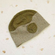 Stripy knitted light wool-rich hat with rolled edge and brooch. Knit in rich colours with subtle coloured flecks. Everyone who wears this hat wears it differently - you can pin the decorative brooch where you like on the hat or off it. | A lovely gift for all ages | Beautiful contemporary women's knitwear | Knit in wool and silk | Cross season knitwear | Summer | Winter | Unusual gift | Valentine's Day | Mother's Day | Birthday gift | Christmas Gift | Style as you like – beret, cloche hat |