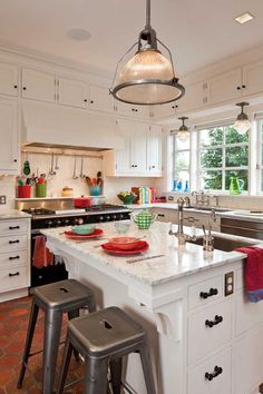 Black glass hardware punctuates white-painted cabinets. The under-counter brackets on the island were modeled on originals in the hallway.