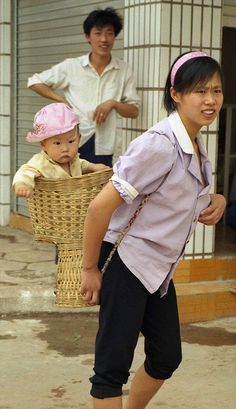 Mother and baby in split level bamboo baby carrier; Mengla, Xishuangbanna Region, Yunnan, China.