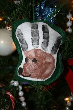 Hand print reindeer ornament. Looks like the print was done on *WHITE FELT* (brown and black paint), then SEWN onto *GREEN FELT* (I think it would be good either stuffed with BATTING or maybe CINNAMON STICKS or some type of POTPOURRI =D and strung with pretty CORDING.