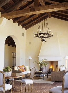 spanish style ... beautiful fireplace + arched doorway + reclaimed ceiling / beams