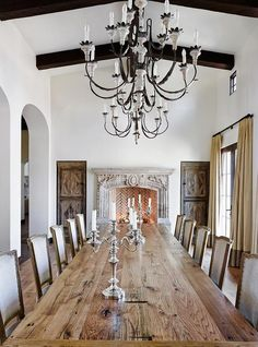 French dining room features a long plank dining table lined with French linen dining chairs illuminated by French candle chandeliers placed in front of a stone fireplace accented with a herringbone firebox flanked by inset cabinets.