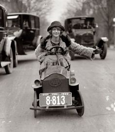 """""""The license plate is almost as large as her automobile, but Miss Mary Bay likes her car because it is easy to park. Miss Bay is shown braving the traffic of Washington."""" January 29, 1924. (She's driving a battery-powered """"Custer Car."""" Invented by Levitt Custer, it was a popular amusement-park ride.) National Photo Co. Collection."""