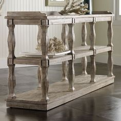 Distressed pine console table with balustrade-style legs and three open display shelves.   Product: Console tableConstruct...