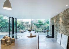 Véranda spacieuse et lumineuse. Intérieur minimaliste, épuré avec un mur en pierre.